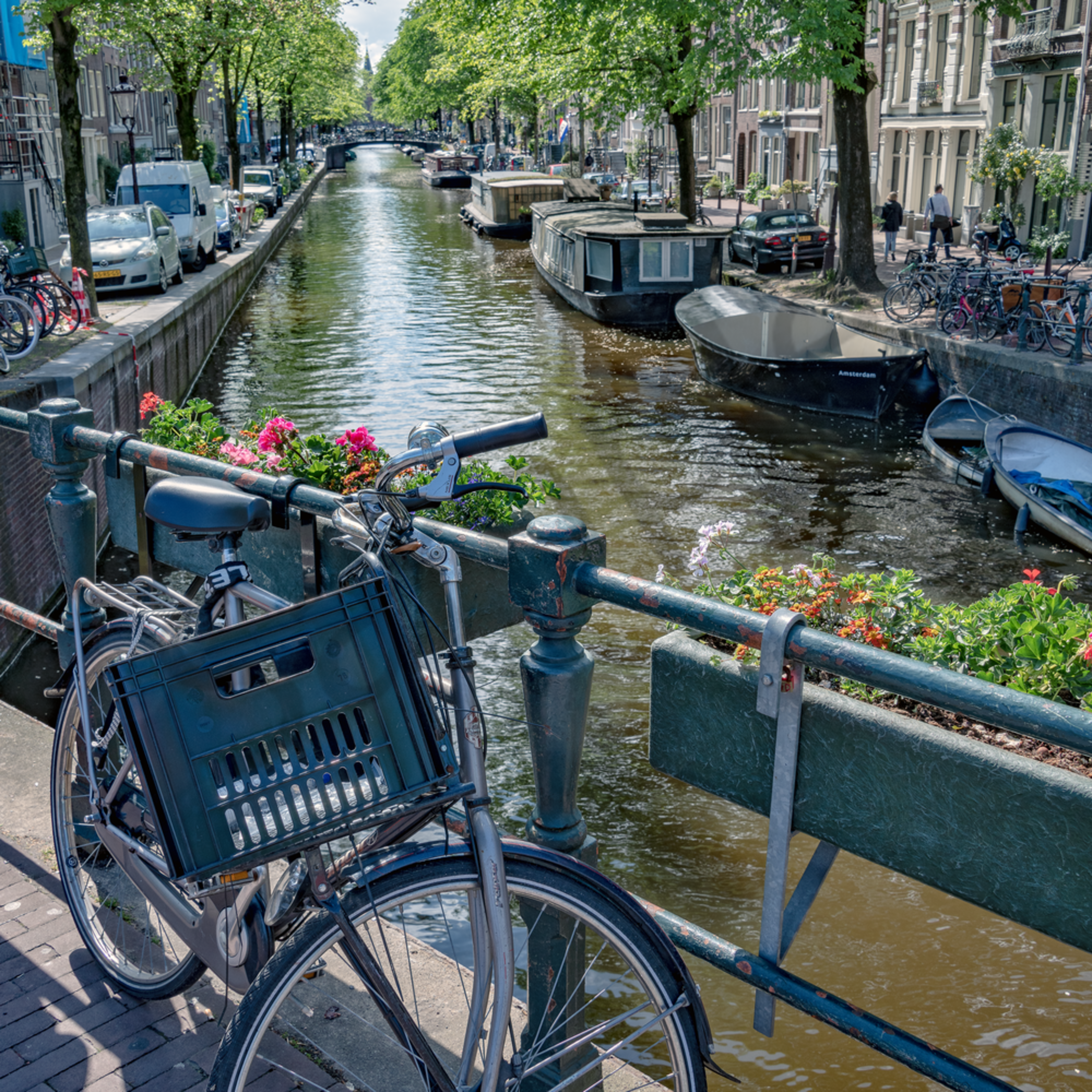 Lone bicycle with flower pots on bridge over canal. amsterdam netherlands atxplx