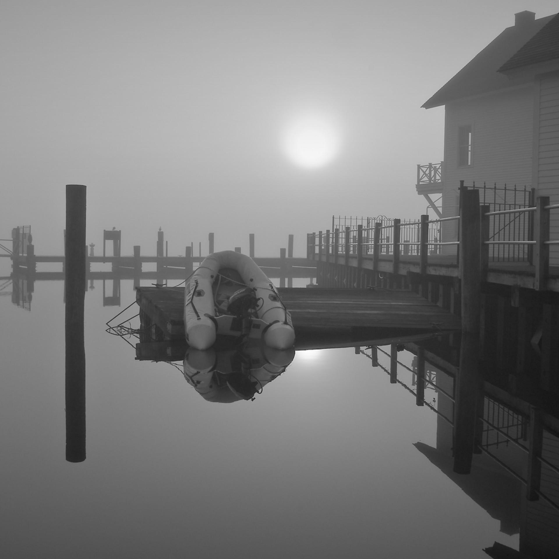 Sunrise over dinghy in morning fog plj7bv
