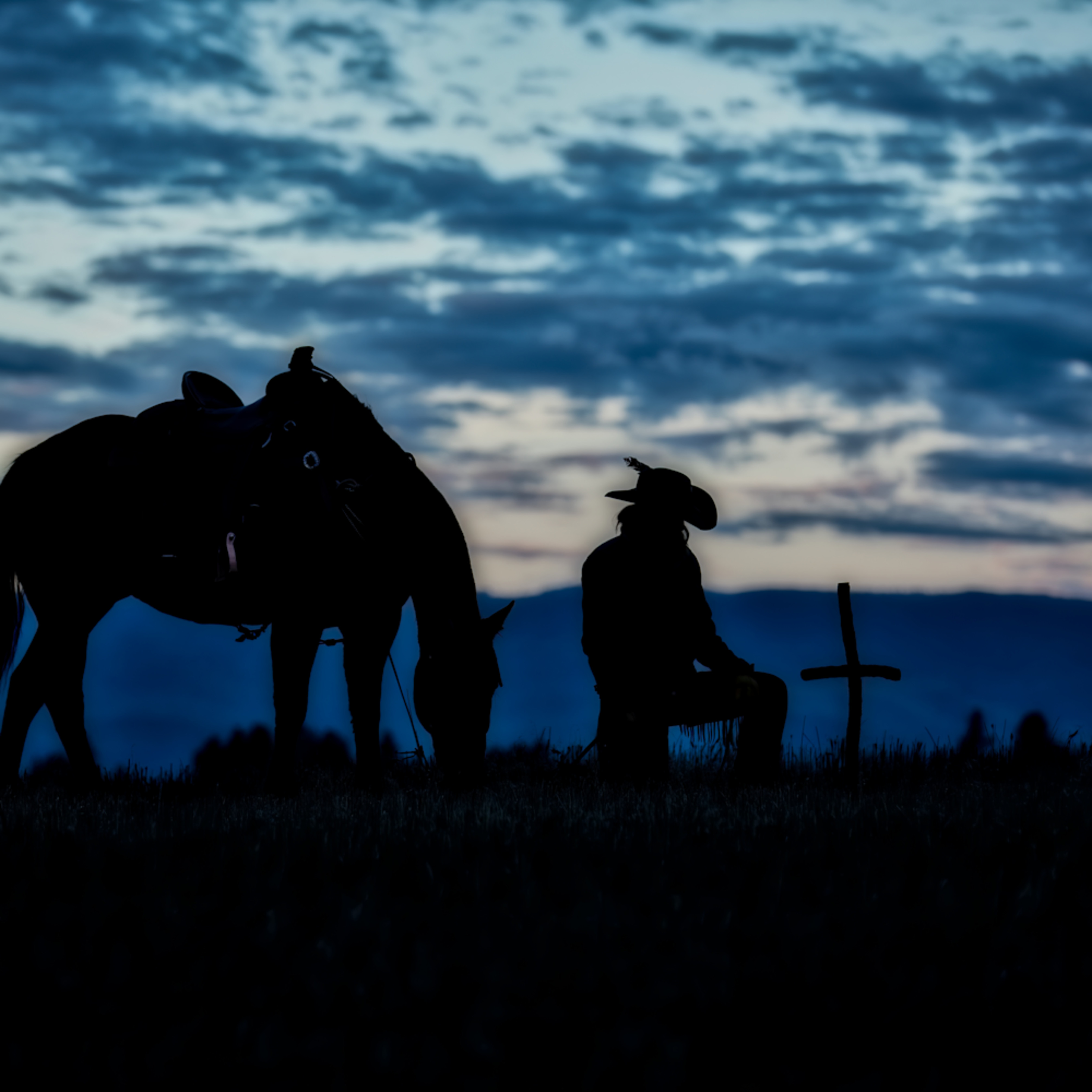 Silhouette of horse and wrangler bowing to cross djyfaj