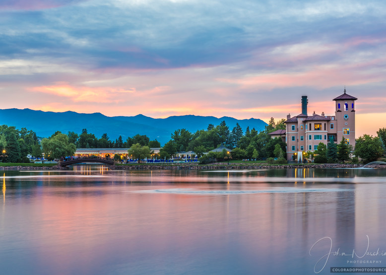 Photograph of The Broadmoor Hotel with Pink and Purple Sunset Reflecting Upon Broadmoor Lake