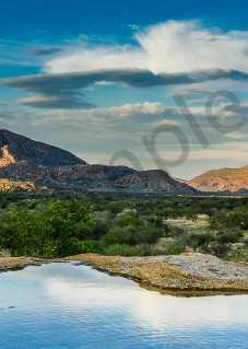 fine art photograph panorama of granite outcrops in a valley with water pooled on rock