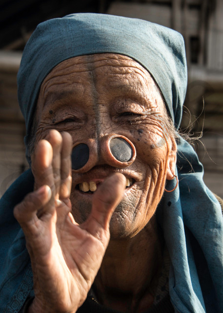 Apatani woman with large nose plugs, smiling and waving.