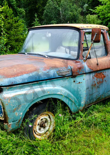 Blue rusting Ford classic pickup truck in field, art photograph