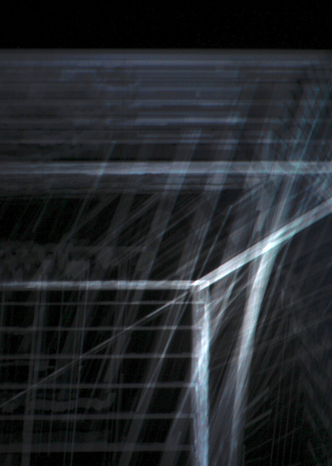 A fine art photograph of refracted projected light of a metallic looking mechanical archway by Michael Toole.