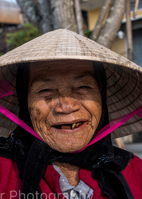 Old woman with conical hat and big smile