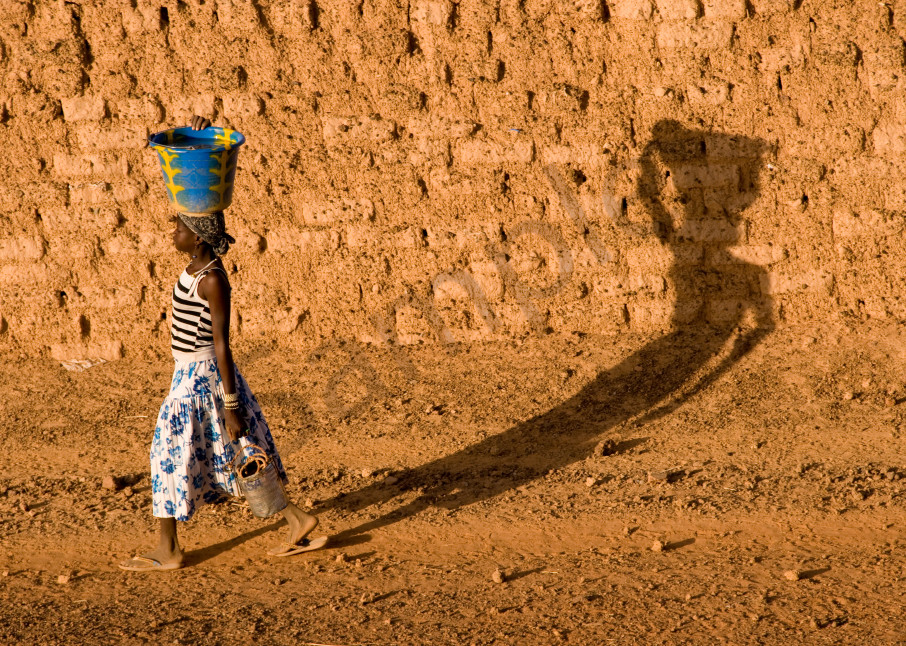 Girl with jug on head casts long shadow on mud wall, in fine art photograph