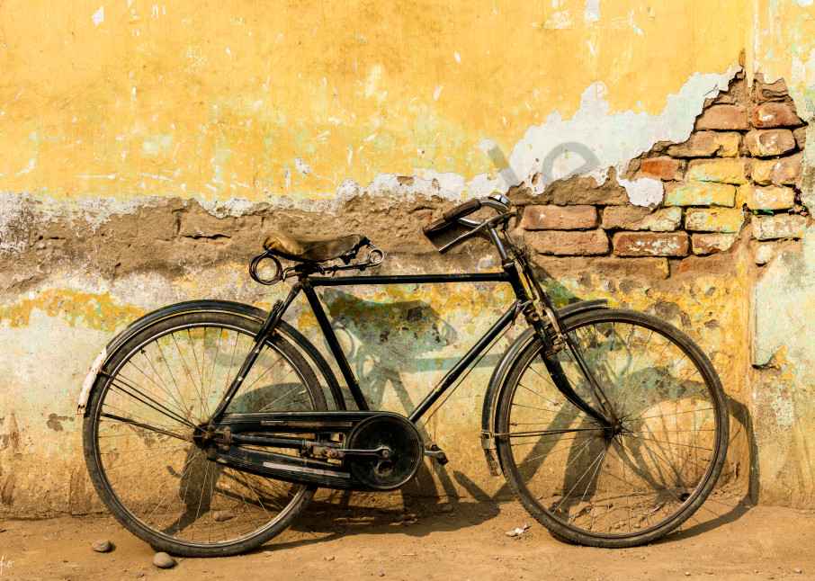 old bicycle by rustic yellow wall in art photograph