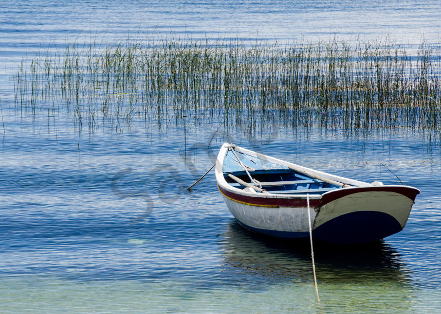 Fine art photograph of rowboat on blue water of Lake Titicaca