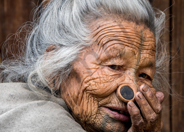 Portrait of old Apatani woman with face tattoo and nose plugs