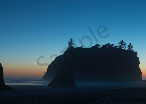 A sliver of moon nearing moonset, shilouetted sea stacks, dusk, Ruby Beach, Olympic National Park, Washington.