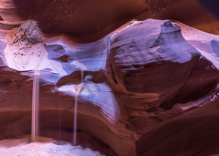Sand pours off a ledge in slot canyon