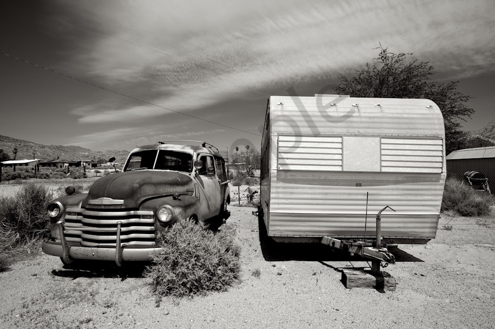 An image taken in Trona, Ca of an old vintage police wagon and an ideal trailer