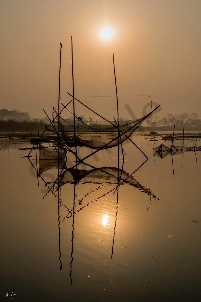 Fishing nets at sunrise reflecting in river water