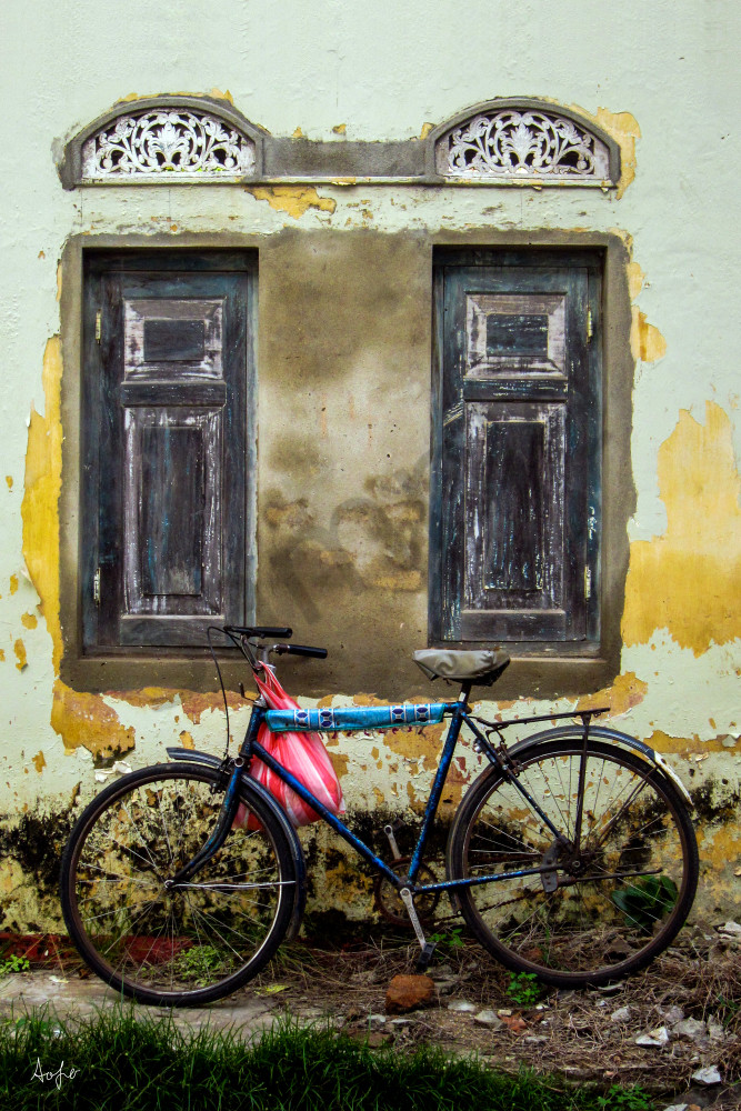 Fine art photograph of old bike under colonial window and crumbling wall