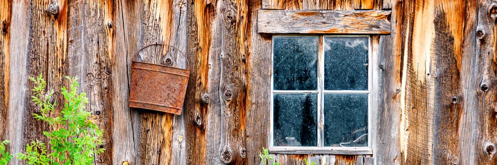 Art photograph, panorama of old bluish window on rustic brown barn