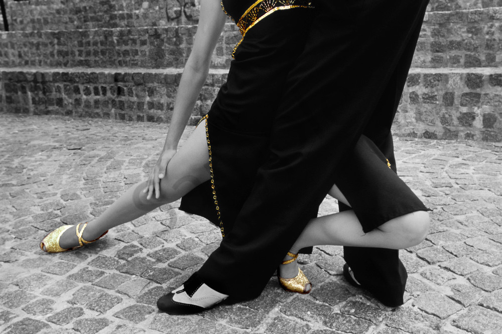 Lower part of Tango dancers intertwined in selective gold color