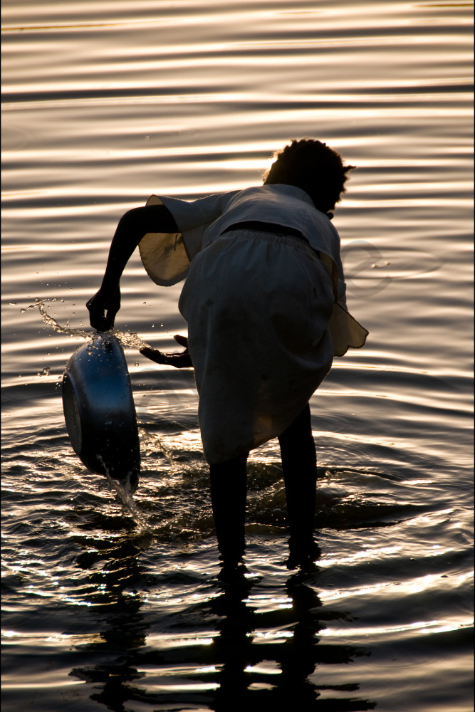 Girl washing bowl in river with gold ripples around her, fine art photograph