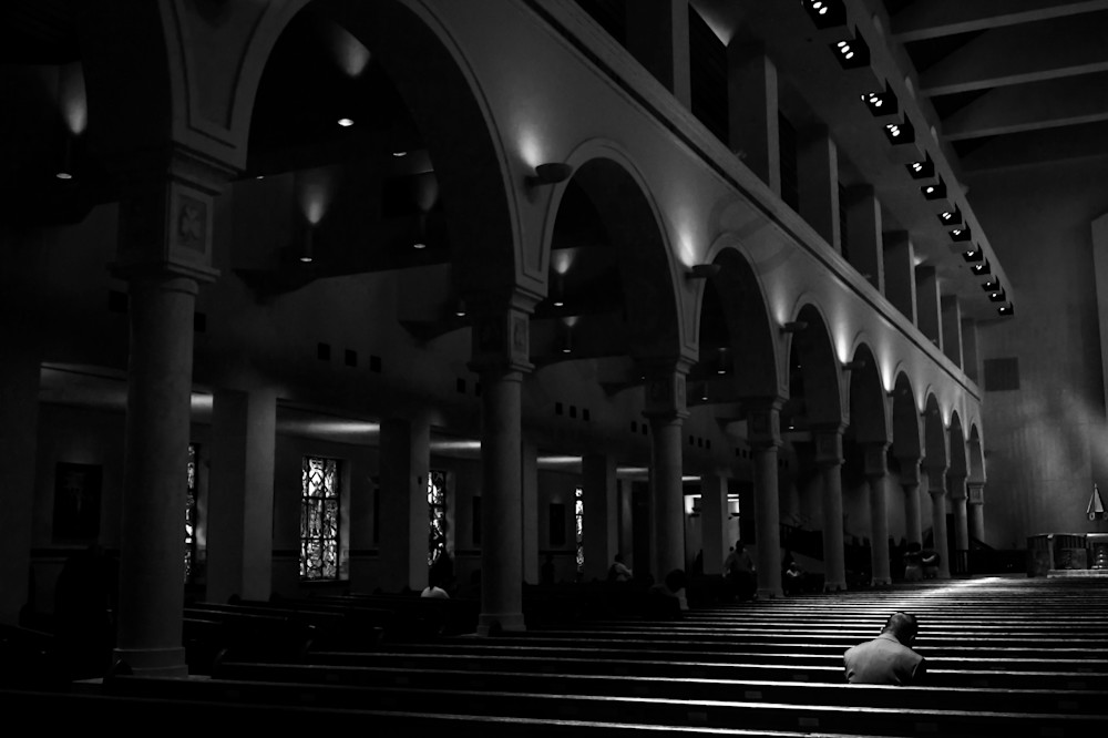 Black & white photograph of a lone worshiper under the basilica arches in Orlando, Florida, for sale as fine art by Sage & Balm