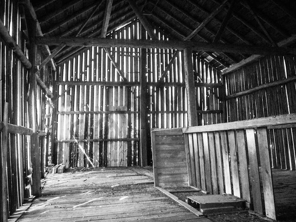 Black & white photograph of light through the interior barn boards of an abandoned rural Ontario barn, for sale as fine art by Sage & Balm