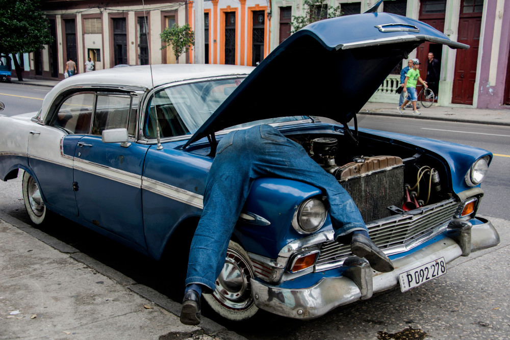 Man in engine of old classic blue car, art photograph print