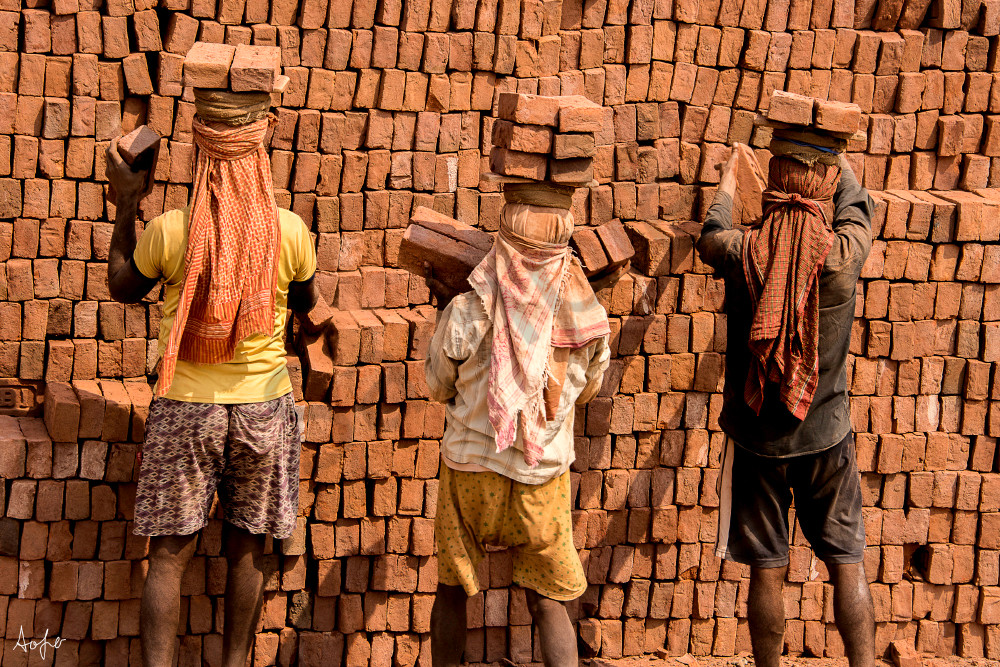 Three Men Carrying Bricks On Their Head, From The Back, In A Fine Art  Photograph Print