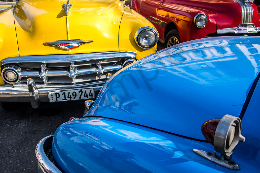Fine art photograph of red, yellow and blue classic cars inHavana, with reflection on hood