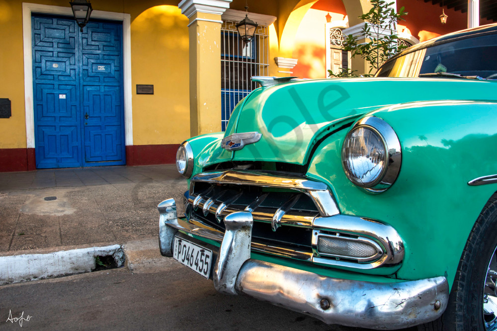 Old classic green Chevy parked in front of arched colonial building