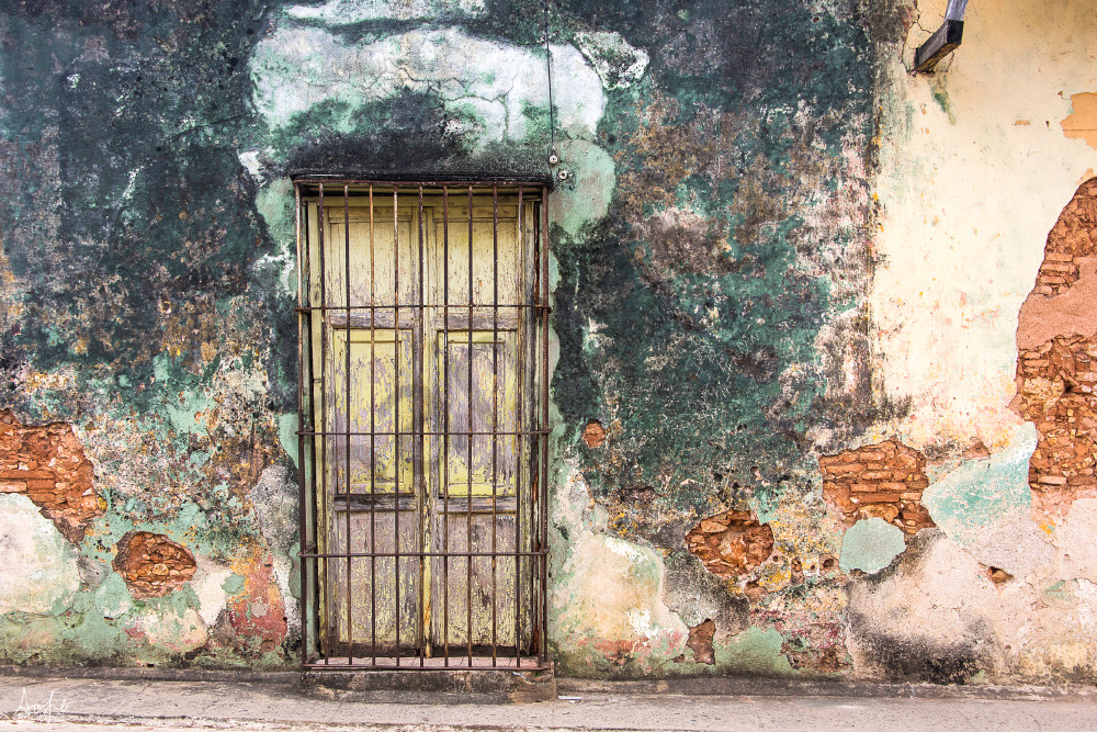 Old Spanish door and iron gate on crumbling wall in fine art photograph.