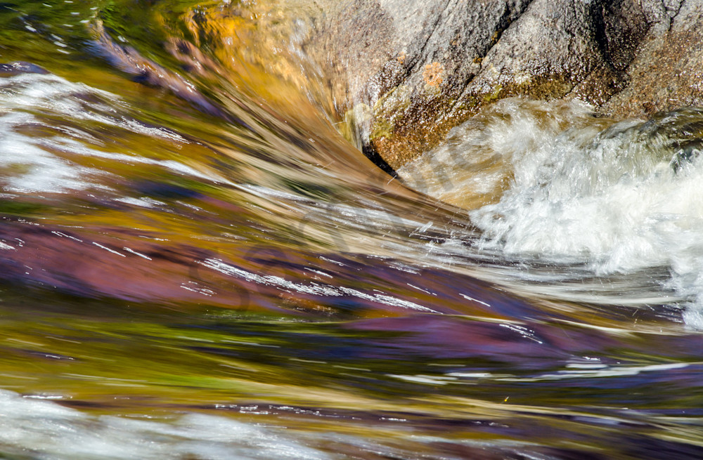 Abstract colors of river water flowing by rock, art photograph from NH