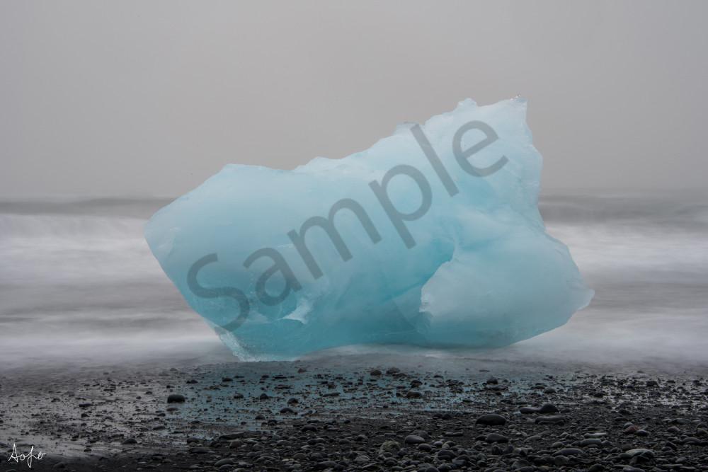 large piece of blue glacier ice on black sand beach, fine art photograph