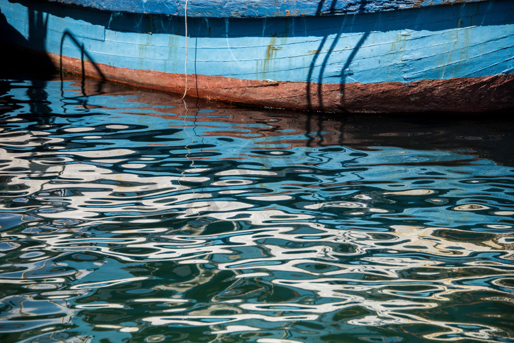 Fine art photograph of reflections on water ripples of blue rowboat