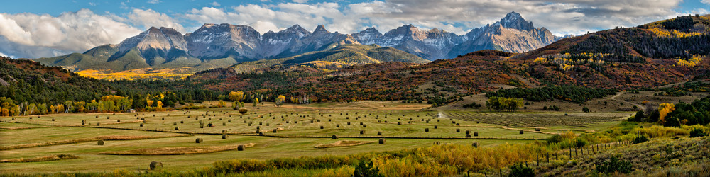 A farmer works his hay field with the might San Juan mountains in the background. Near Ridgway Colorado