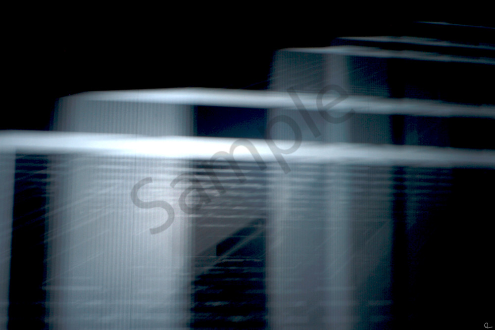 Fine Art Photograph Of A Moving Metallic Light Projection Against Dark Stark Background