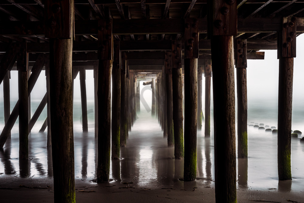 Eerie view under pier in fog
