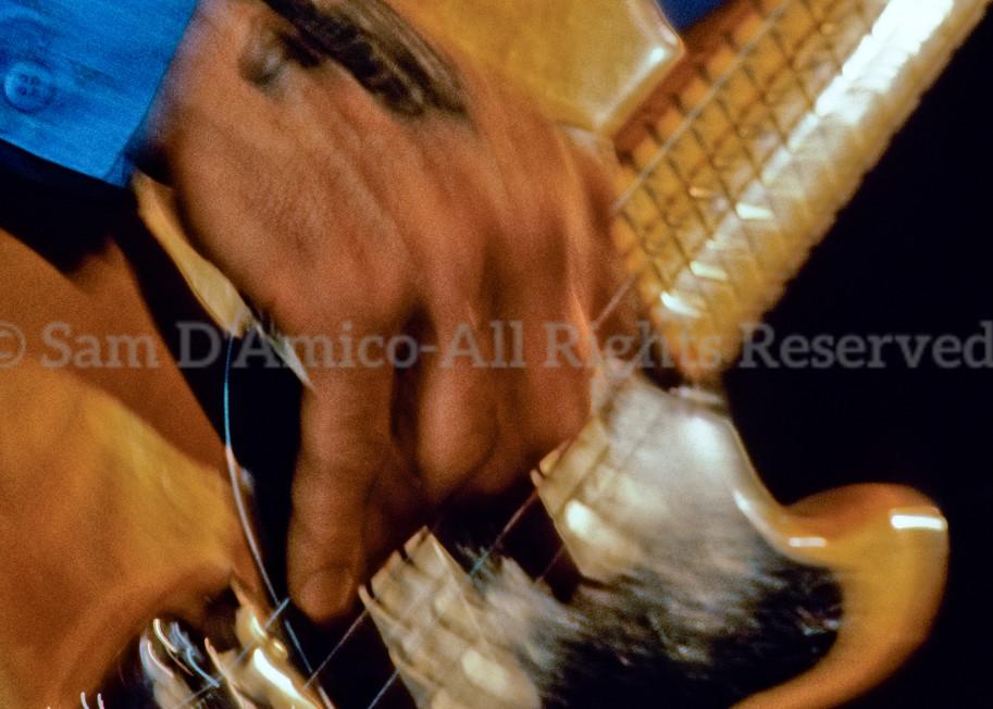 A Tattooed Hand Plays A Bass Guitar