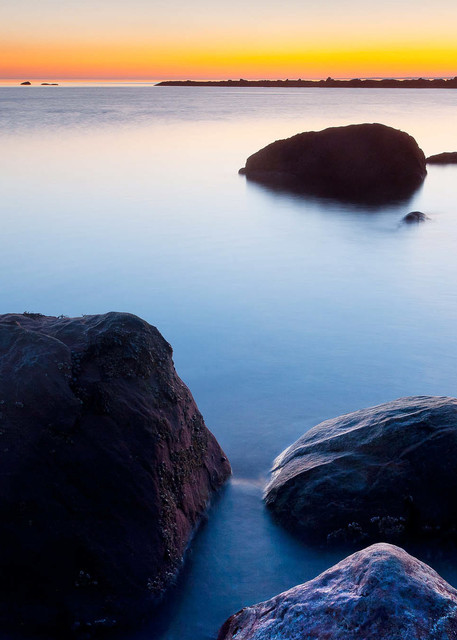 Peter Wnek photograph of the quiet water of Meigs Point at Hammonasset State park in Connecticut radiates in yellow and orange against the blue water of Long Island Sound.