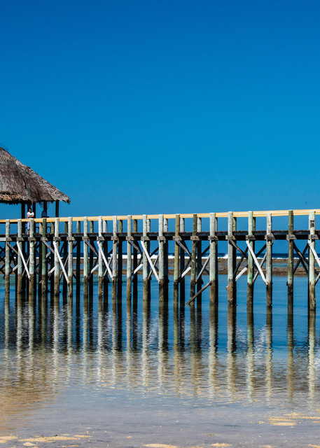 The reflection of a Pier on the ocean is available as a fine art photograph for sale