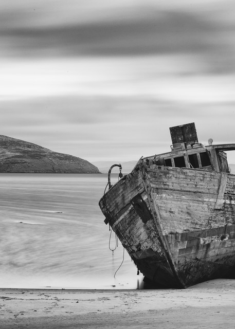 There were multiple stories about this ship, but the most believable is that it's an old minesweeper, ran aground and left there when whoever had finished with it.