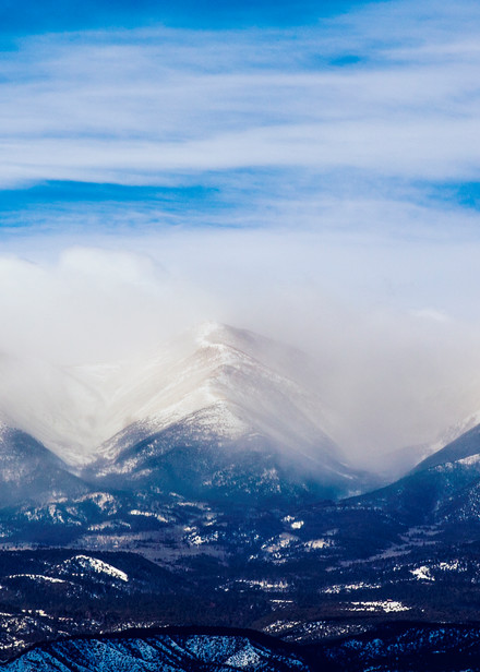 Winter storms seem to delicately dust the peaks of mountain peaks in Colorado under a beautiful, calm blue sky.