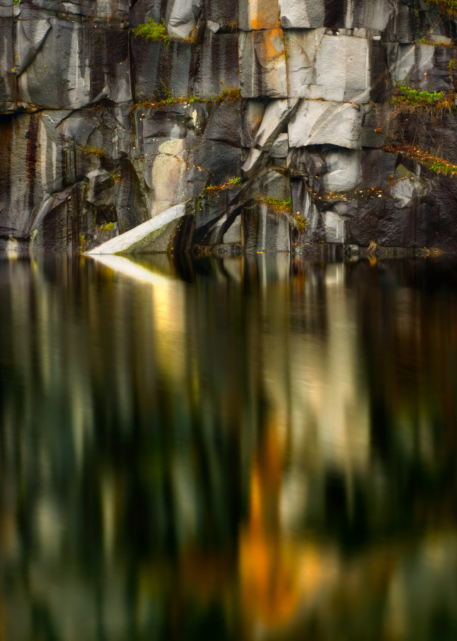 Reflections of stone quarry in stillness of pond