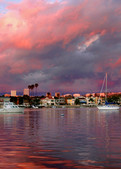 a panorama of boats in newport beach under red skies.