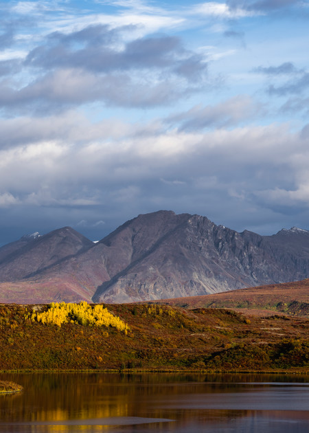 Autumn sunrise illuminates Round Tangle Lake and the Amphitheater Mountains along the Denali Highway in Southcentral Alaska. Morning.