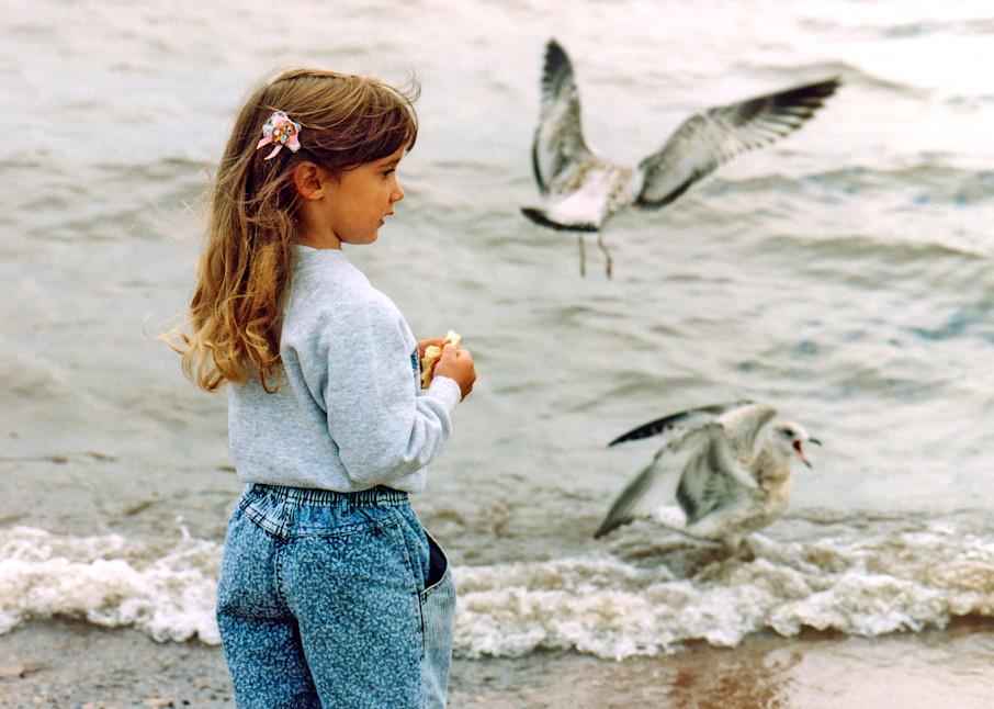 Pretty little girl feeding gulls on the shore — fine art photograph