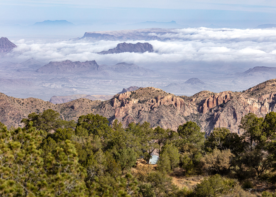 A campsite overlooking clouds acting like waves of water against the mountains at Big Bend National Park in Texas.