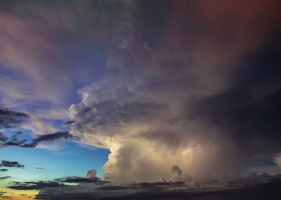 Watching a sunset as a thundercloud with lightning moves in
