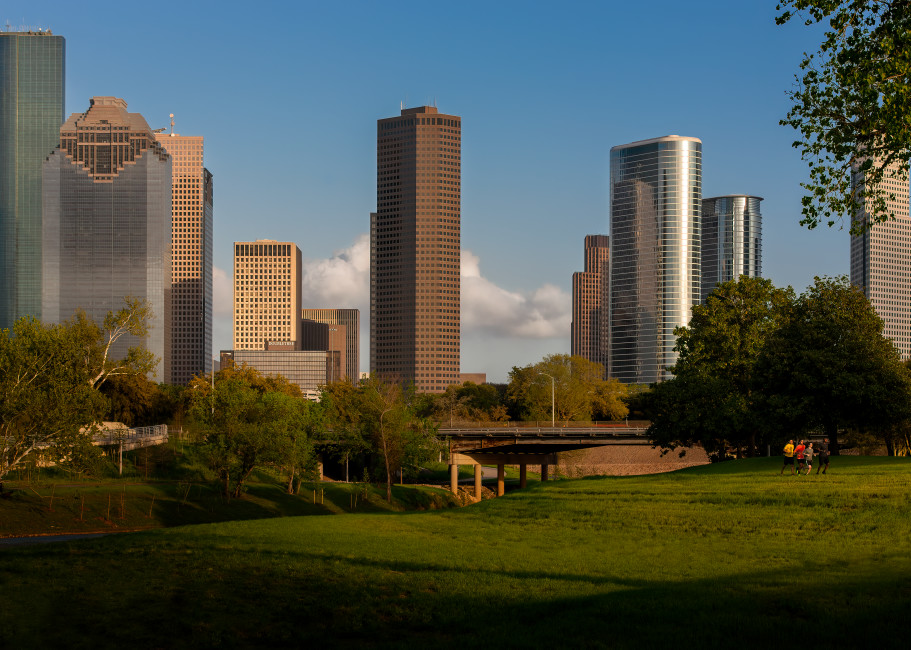 Runners along Allen Parkway in BRunners along Allen Parkway in Buffalo Bayou Park  with The Downtown Houston Skyline Behind Themuffalo Bayou Park  with The Downtown Houston Skylibe Behind Them