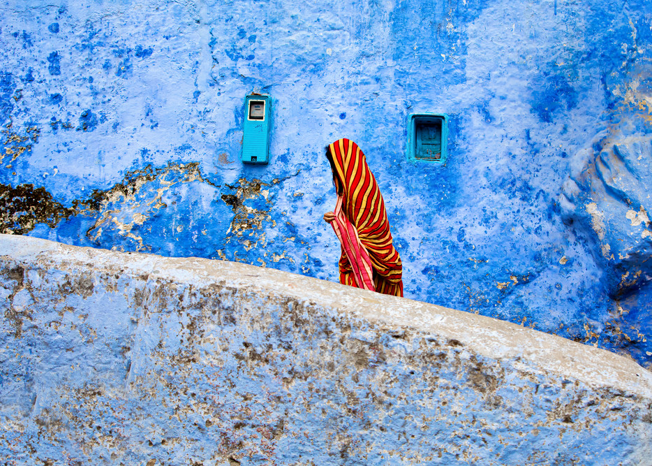 Travel photograph of woman in bright red and yellow chador walking in front of blue wall in Chefchaouan Morocco the blue city
