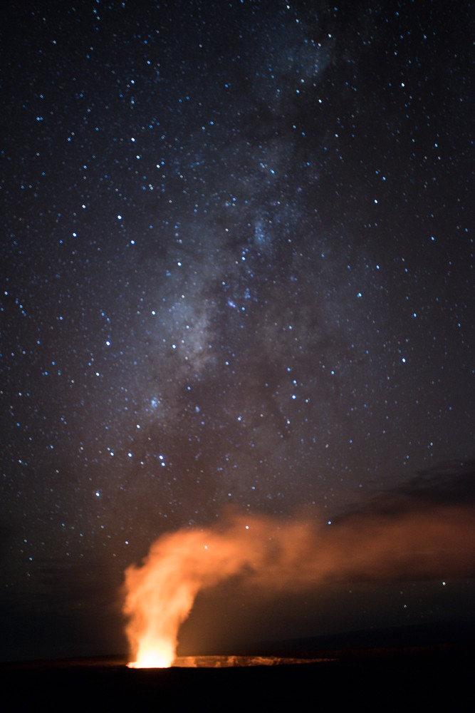 Hawai'i Volcanoes National Park, Big Island of Hawaii, Hawaii; the night sky, stars and the milky way are visible above the glowing lava lake within the Halemaʻumaʻu crater on Kīlauea volcano