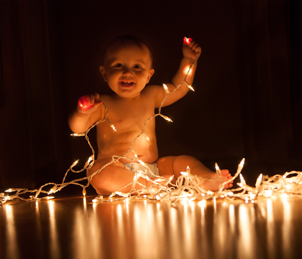 Happy toddler with Christmas tree lights - fine art photograph