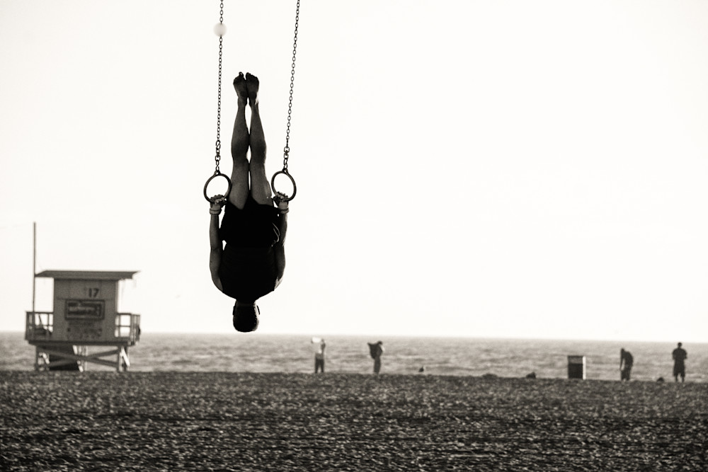 Silhouette of a person swinging on rings